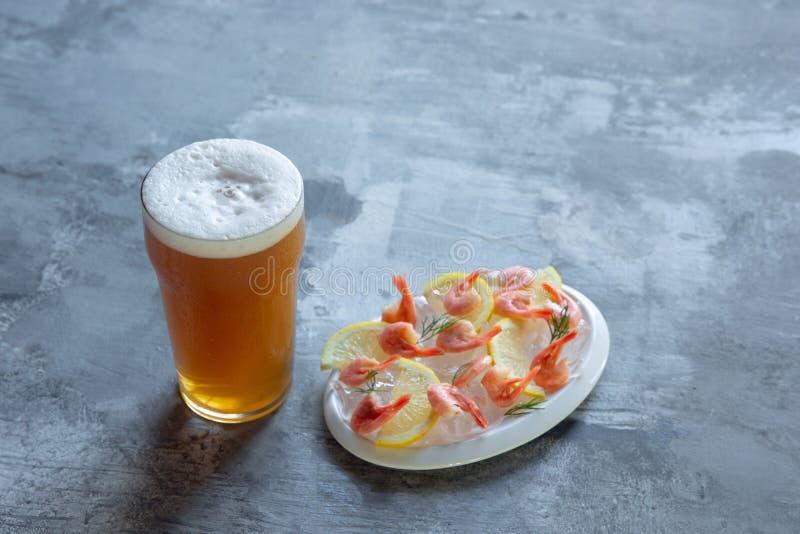 杯在白色石背景的低度黄啤酒 图库摄影