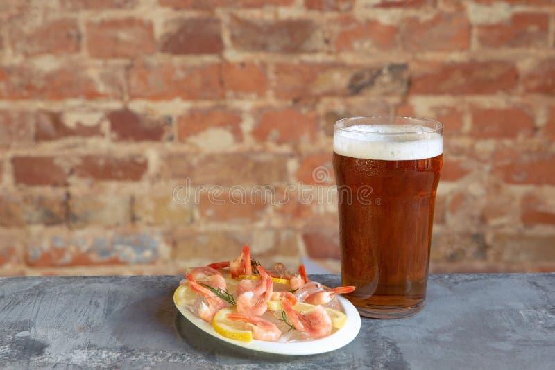 杯在白色石背景的低度黄啤酒 免版税图库摄影