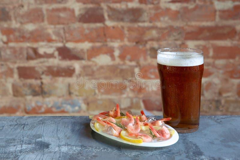 杯在白色石背景的低度黄啤酒 库存图片