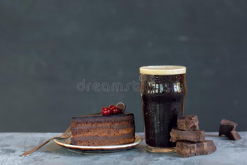 杯在石桌和灰色背景上的黑啤酒 库存照片