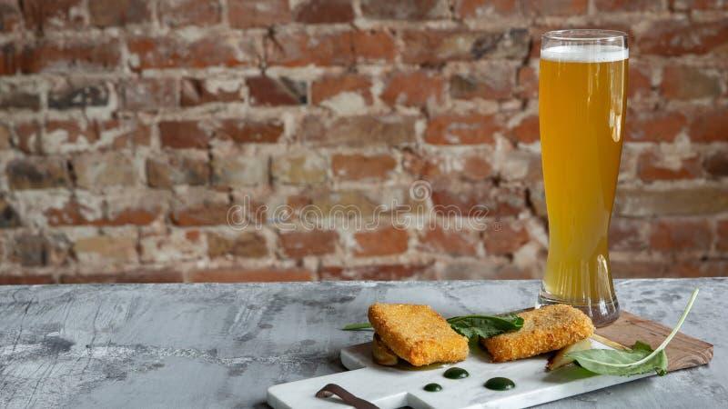 杯在石桌和砖的背景的低度黄啤酒 免版税图库摄影