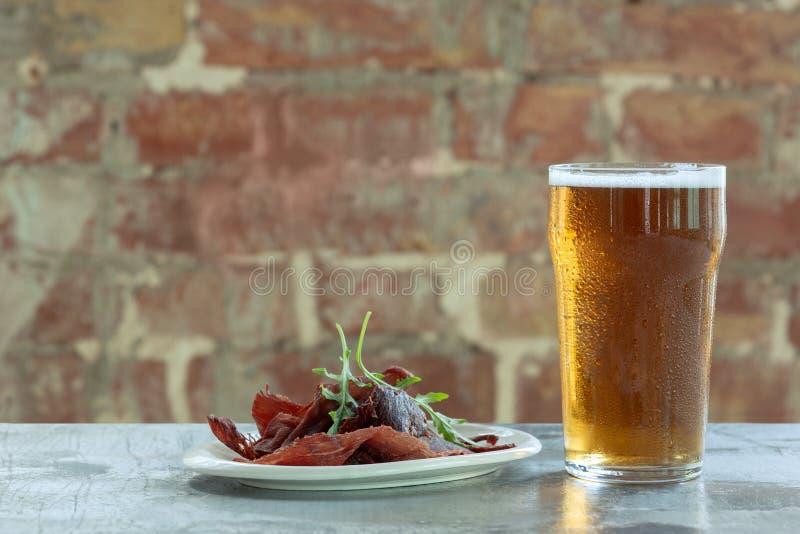 杯在石桌和砖的背景的低度黄啤酒 免版税库存图片