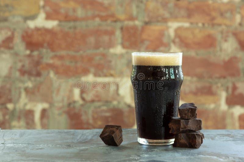 杯在石桌和砖的背景的黑啤酒 库存照片