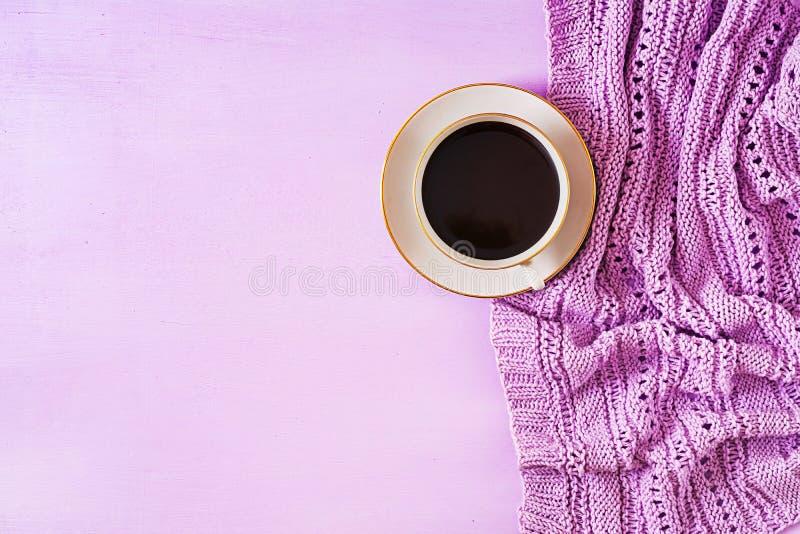 杯在紫罗兰色桌,照片的关闭上的热的咖啡编织了有杯子的毛线衣 库存照片