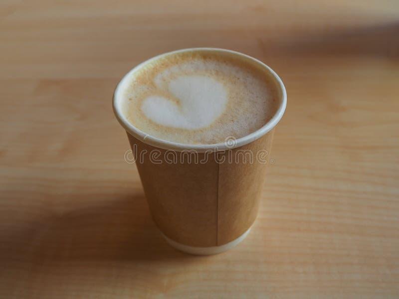 杯在纸外带的杯子的热奶咖啡在木桌上 免版税库存照片