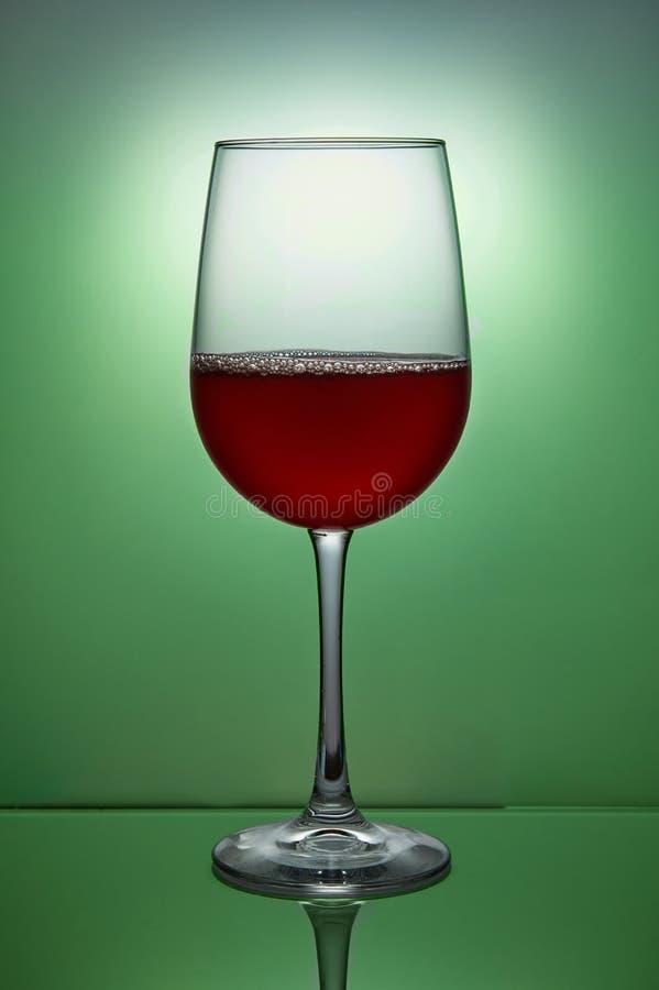 杯在绿色的红酒 免版税库存图片