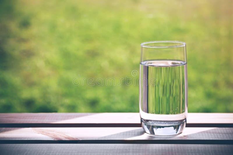 杯在绿色自然本底的纯净的水 库存图片