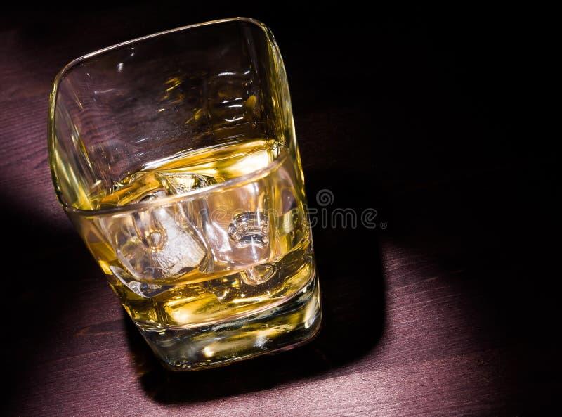 杯在老木桌和坚硬光上的威士忌酒 库存图片