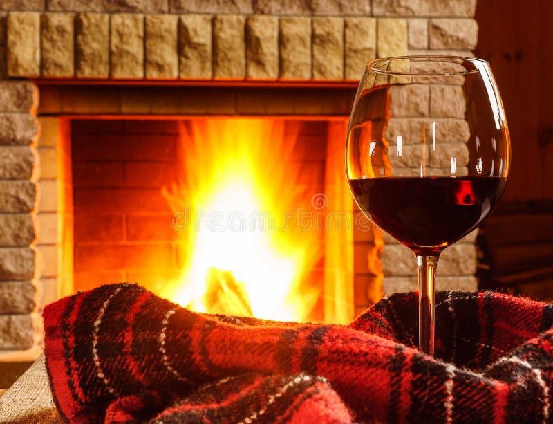 杯在舒适壁炉前的红葡萄酒 免版税库存图片