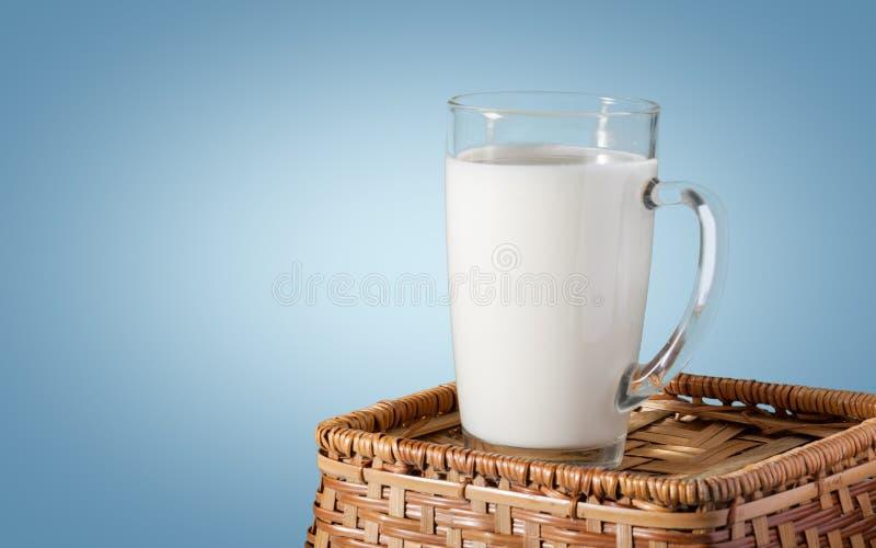 杯在蓝色背景的新鲜的牛奶 免版税图库摄影