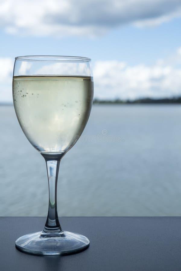 杯在表上的白葡萄酒在海边餐馆 免版税图库摄影