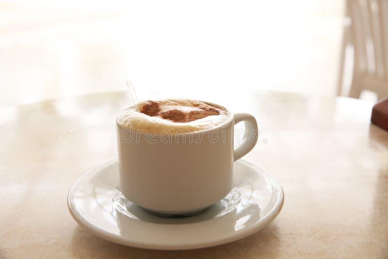 杯在表的热奶咖啡 库存照片