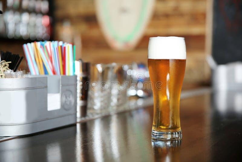 杯在酒吧柜台的啤酒在咖啡馆 免版税库存照片