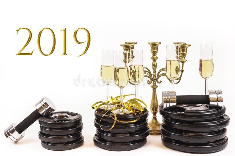 杯在重量板材和哑铃的香槟 新年决议的概念2019年 免版税库存照片