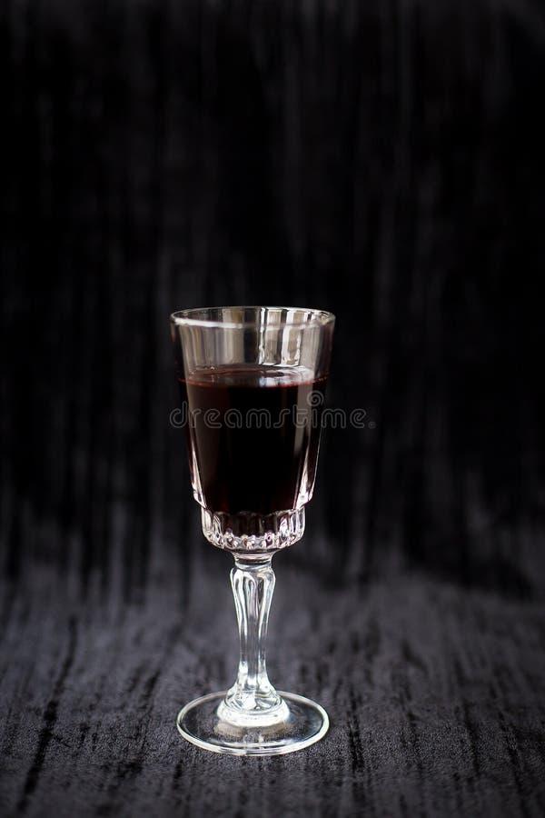 杯在黑天鹅绒背景的红酒,特写镜头 库存照片