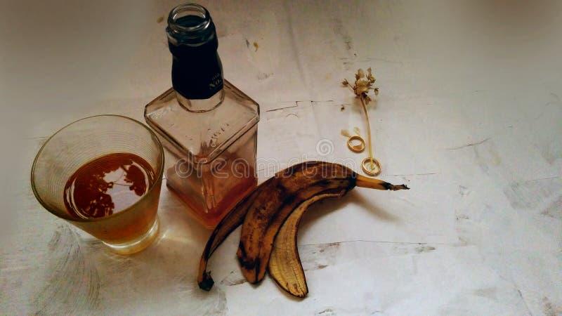 杯威士忌酒、瓶和结婚戒指在烟在灰色背景 库存照片