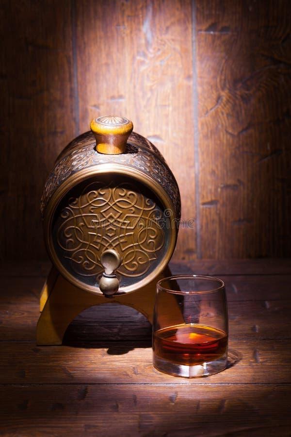 杯威士忌酒和小桶在木桌上 库存照片