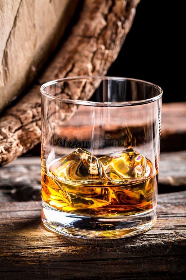 杯威士忌酒和老橡木桶 免版税库存图片