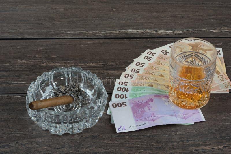杯威士忌酒和金钱与古巴雪茄在一张灰色木桌上 顶视图 免版税库存照片