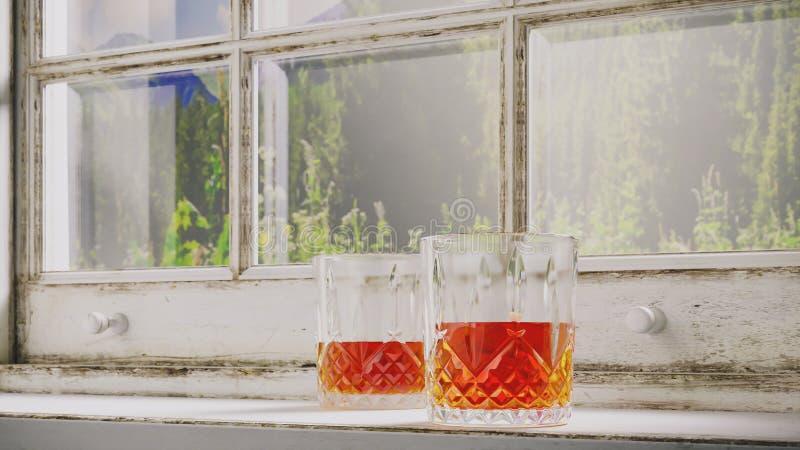 杯威士忌酒在窗台的白兰地酒立场,点燃由太阳以一个老破旧的土气窗口为背景 免版税库存照片