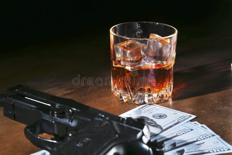 杯威士忌酒或科涅克白兰地,枪,与金钱的纸牌在黑镜子桌上 罪犯的概念 免版税图库摄影