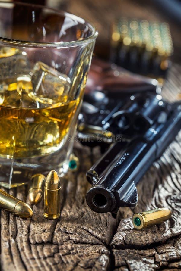 杯威士忌酒科涅克白兰地或波旁酒与左轮手枪和子弹 库存照片