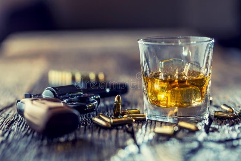 杯威士忌酒科涅克白兰地或波旁酒与左轮手枪和子弹 免版税库存照片