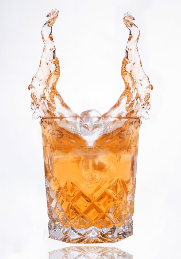 杯威士忌酒飞溅 免版税库存图片