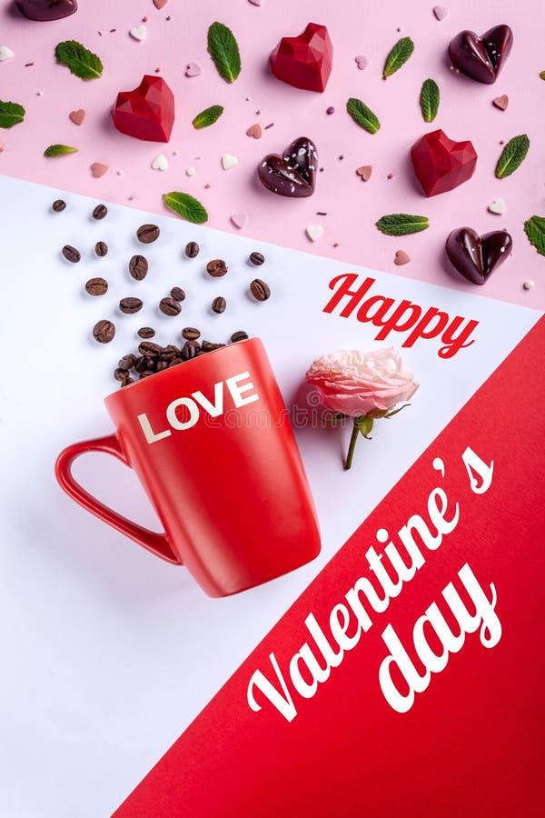 杯子、咖啡豆、桃红色玫瑰和被塑造的巧克力糖心脏,顶视图 情人节浪漫贺卡 图库摄影