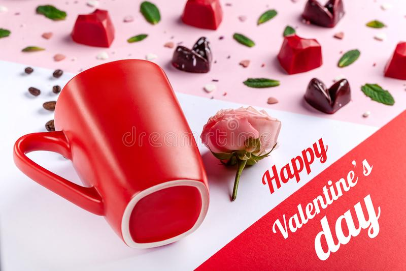杯子、咖啡豆、桃红色玫瑰和被塑造的巧克力糖心脏,顶视图 情人节浪漫贺卡 库存图片