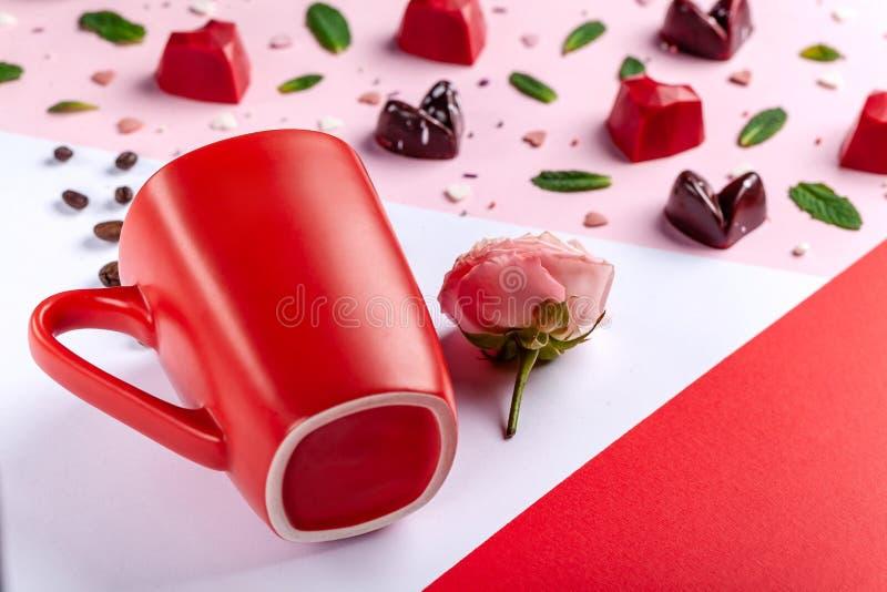 杯子、咖啡豆、桃红色玫瑰和被塑造的巧克力糖心脏,顶视图 情人节浪漫贺卡 免版税库存照片