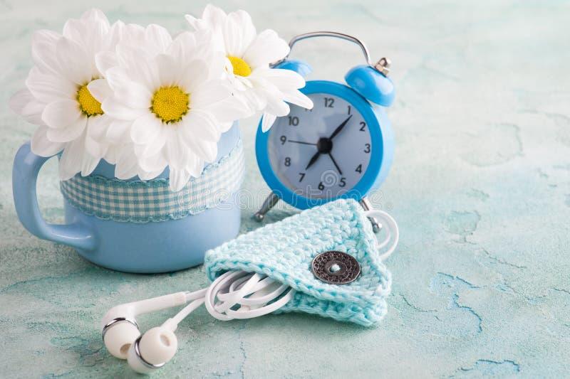 杯子、蓝色闹钟和花 图库摄影