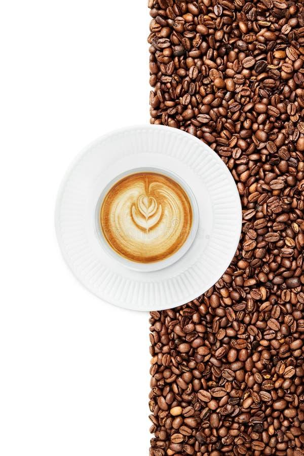 杯子一晚在白色背景的咖啡豆suraunded的一块白色板材 库存照片
