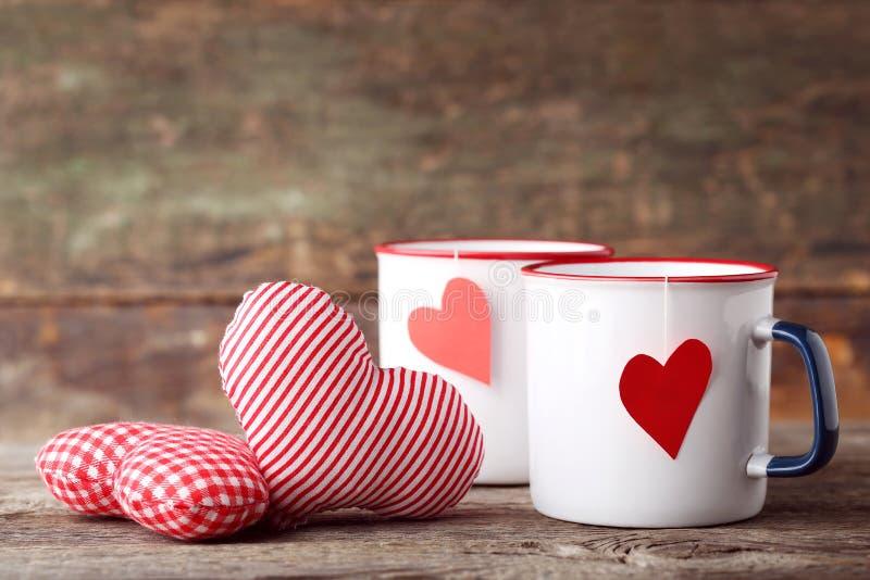 杯子与织品心脏的茶 免版税图库摄影
