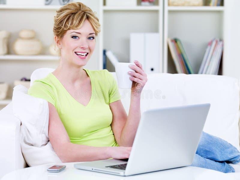 杯子使用妇女的膝上型计算机茶 免版税图库摄影
