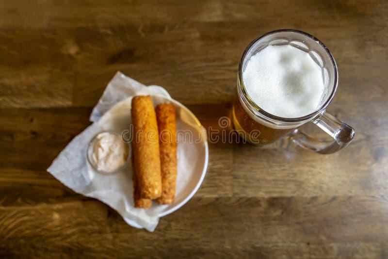 杯子冷的储藏啤酒,在被弄脏的背景,油煎的酥脆乳酪快餐用一个调味汁,在一张木桌上,在客栈 ?? 免版税库存照片