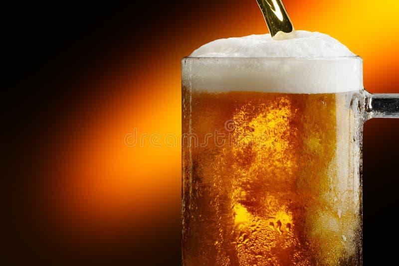 杯子冷的在黑暗的背景的工艺低度黄啤酒 免版税图库摄影
