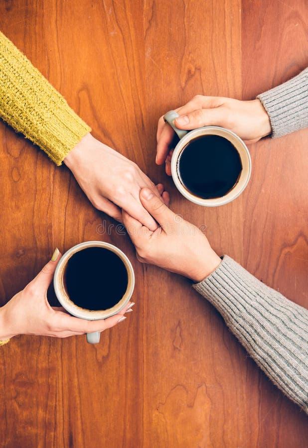 从杯子和举行手的人饮用的咖啡在浪漫日期 库存照片