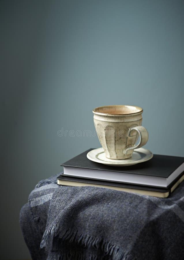杯子咖啡和书在灰色羊毛格子花呢披肩 免版税库存图片