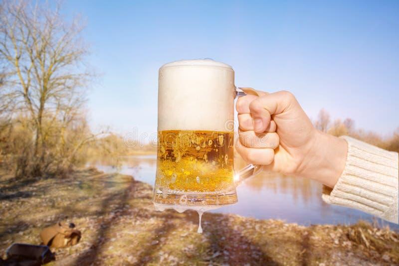 杯子啤酒在手中在河的背景 库存照片