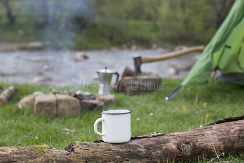 杯子在日志站立靠近火在露营地 库存照片