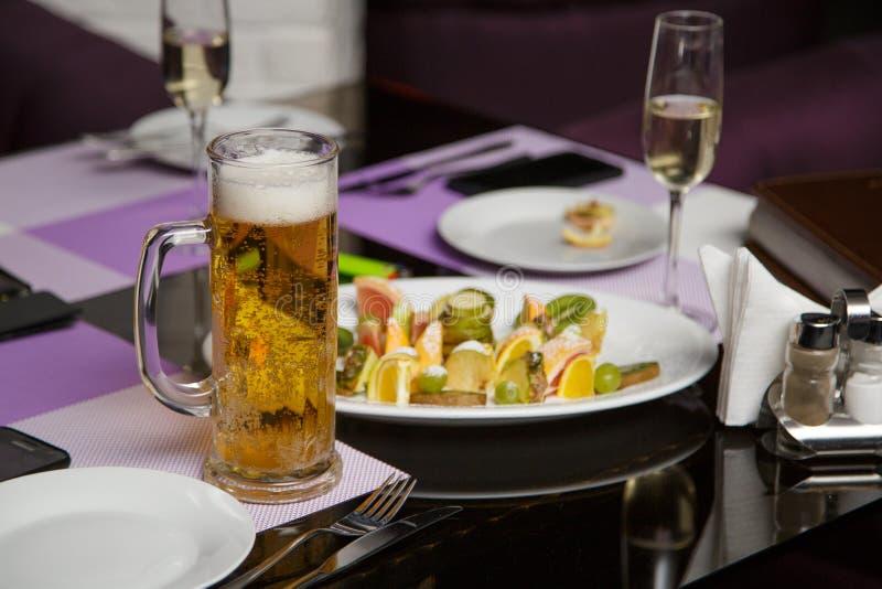 杯子在玻璃桌上的啤酒与快餐 免版税图库摄影