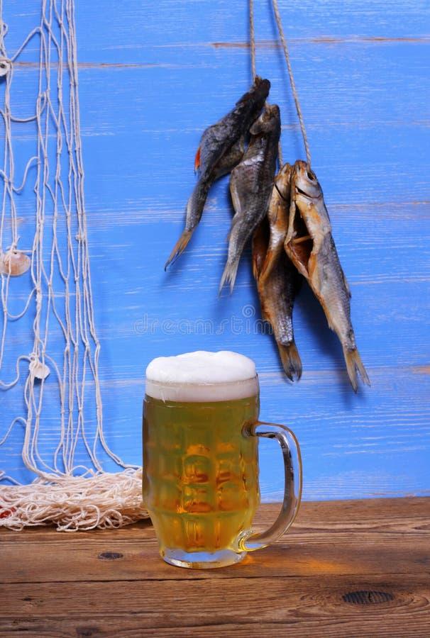 杯子在蓝色背景的啤酒与干rudd鱼 库存图片