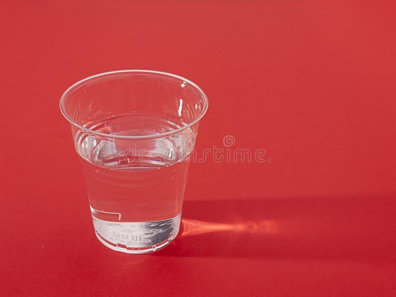 杯子新鲜的超出塑料红色sidelit水 免版税库存图片