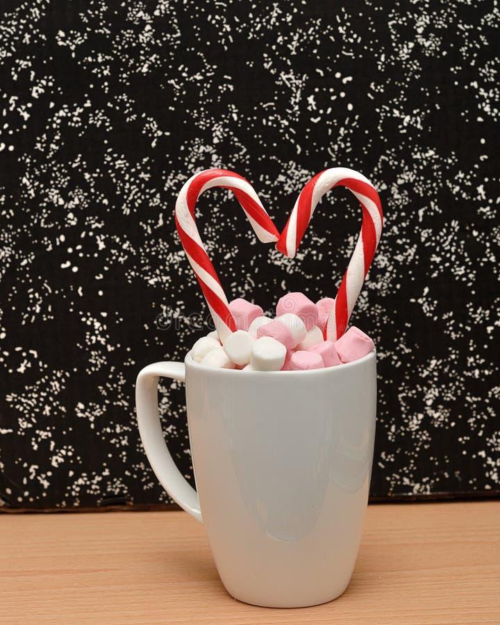 杯子用小蛋白软糖和棒棒糖填装了 免版税库存照片