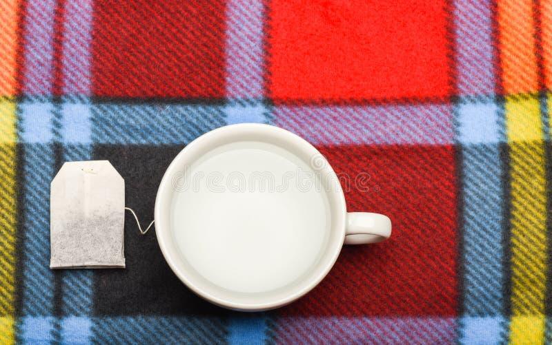 杯子用开水和茶袋填装了在五颜六色的格子花呢披肩背景 茶时间概念 酿造茶的过程  免版税库存照片