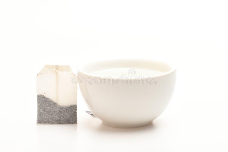 杯子用开水和茶袋填装了在白色背景 杯或白色瓷杯子有透明热水的和 免版税库存照片