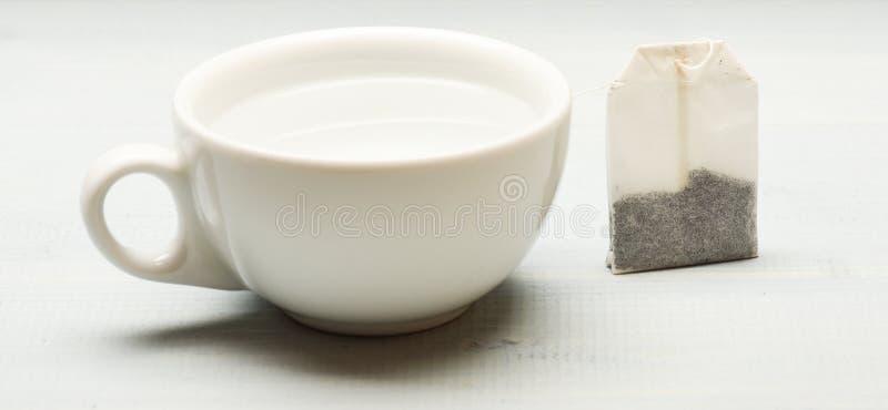 杯子用开水和茶袋填装了在白色背景 茶时间概念 酿造在陶瓷杯子的茶的过程 库存图片