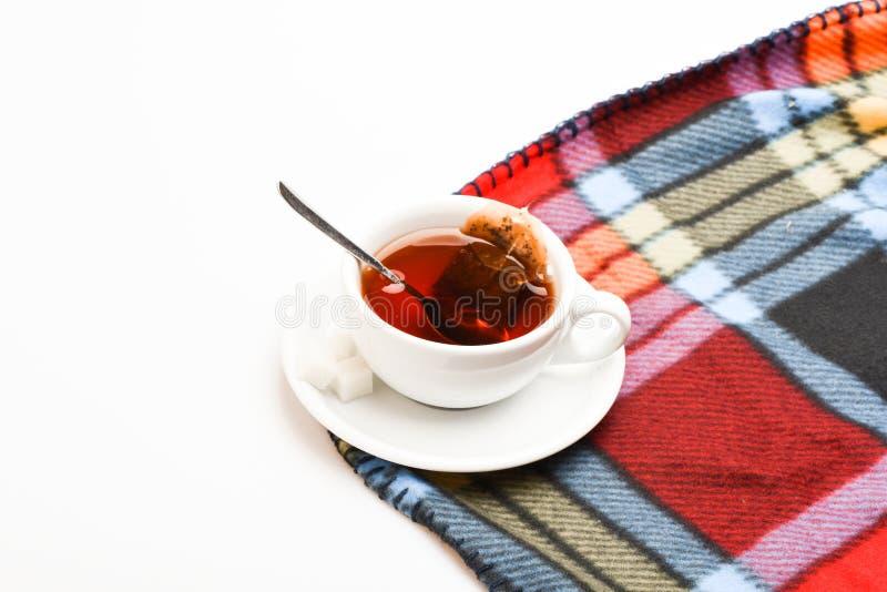杯子用热的黑色酿造的茶和匙子填装了在五颜六色的舒适格子花呢披肩背景 有被浸洗的袋子的茶杯子茶  免版税库存照片