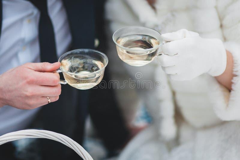 杯子用茶在新娘和新郎的手上在冬天 免版税库存照片
